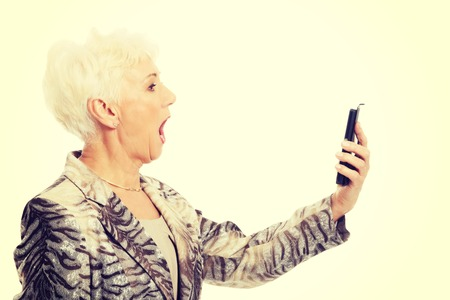 lady on phone: An old elegant lady using mobile phone Stock Photo