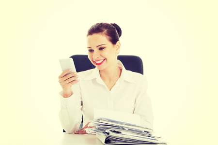 Beautiful business woman sitting by a desk with stack of papers with mobile phone. photo