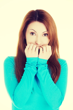 Stressed young woman eating her nails. photo