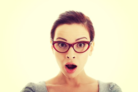 shocked face: Young casual woman in eyeglasses expresses shock