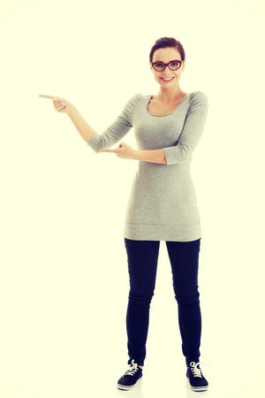 aside: Beautiful casual woman in eyeglasses pointing aside