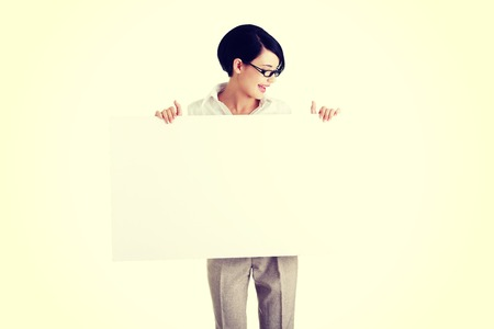 Smiling young business woman showing blank signboard Stock Photo - 29434109