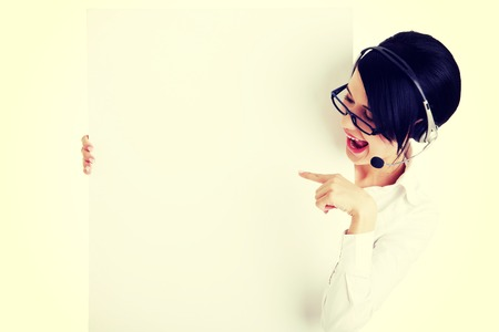 Pretty young call center worker wearing a headset and holding blank sign board Stock Photo - 29434110