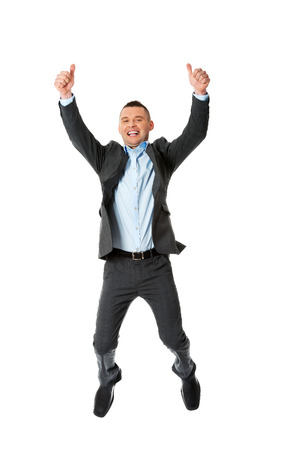 Happy businessman jumping in the air with thumbs up photo
