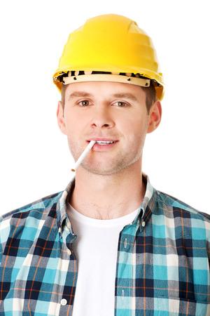 Craftsman in helmet smoking cigarette photo