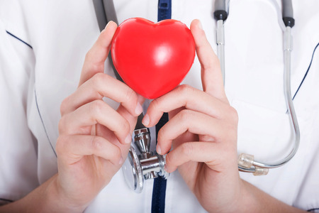 Red heart held by a female doctor. Close up. photo