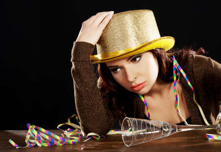 Young drunk woman sitting by a desk with empty champagne bottle after celebrating new years eve.  photo
