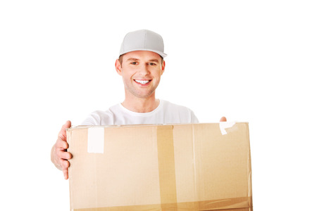 delivery service: Young attractive courier guy delivering brown boxed parcel