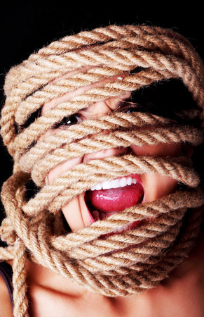 Tied up scared woman face. Violence concept. photo