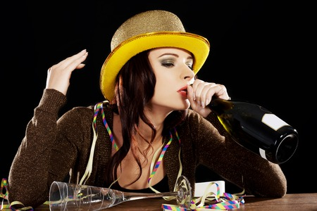 Young drunk woman sitting by a desk with empty champagne bottle after celebrating new years eve. On black background. photo