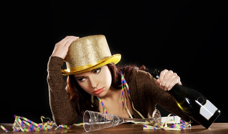 drunk woman: Young drunk woman sitting by a desk with empty champagne bottle after celebrating new years eve. On black background. Stock Photo
