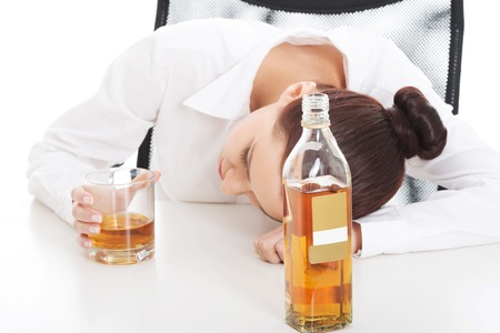 irresponsible: Alone young businesswoman in depression, drinking alcohol.