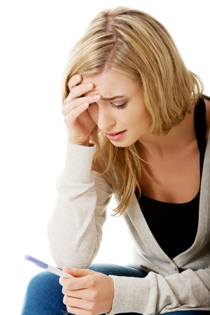 Sad young woman holding pregnancy test feeling hopeless