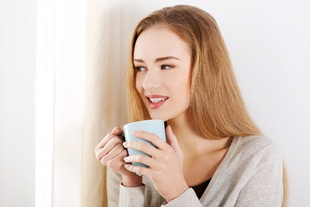 Beautiful caucasian woman drinking hot coffee or tea and looking through window. Indoor background. photo