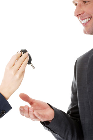 Car salesman handing over the keys for a new car to a young businessman photo