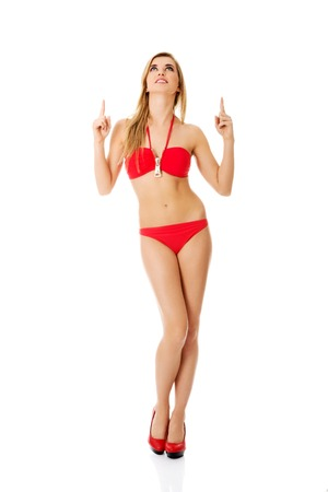 Pretty and beautiful young woman in a swimsuit pointing a finger on copy space photo