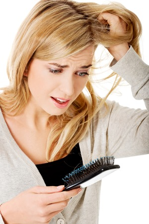 Stressed young woman loosing hair photo