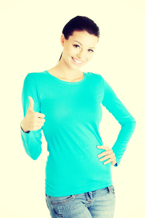 Beautiful young success woman gesturing thumbs up standing on white background. photo