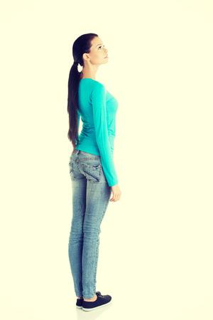 mujer de espaldas: Mujer ocasional joven desde atr�s mirando hacia arriba, aislado en blanco Foto de archivo