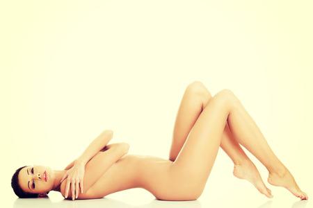mujeres desnudas: Sexy mujer desnuda en forma con la piel limpia y sana acostado, aislado en blanco Foto de archivo