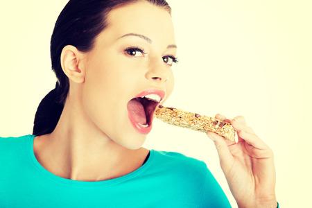 barra de cereal: Mujer joven que come la barra de caramelo de cereales, aislado en blanco Foto de archivo