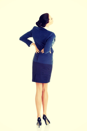 back ache: Businesswoman with back ache after long work. Isolated on white Stock Photo