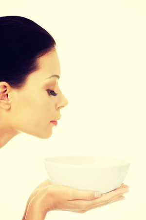 Beautiful young woman holding bowl and smells photo