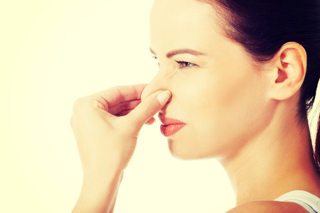 hyperhidrosis: Portrait of a young woman holding her nose because of a bad smell.
