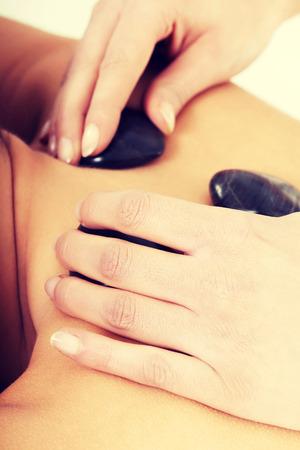 Beautiful woman lying on spa salon having stone massage. Spa concept. photo