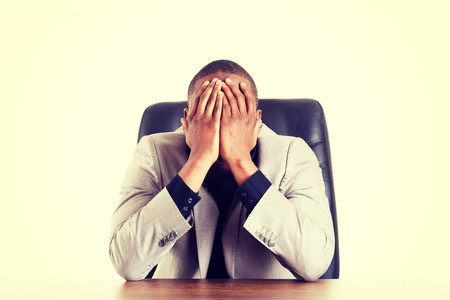Sad, tired or depressed businessman at the desk. photo