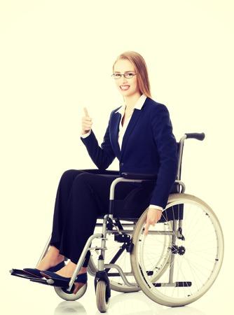 Beautiful caucasain business woman sitting on wheelchair. Isolated on white. photo