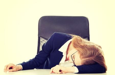 mujeres trabajando: Dormir mujer de negocios junto a la mesa. Aislado en blanco.