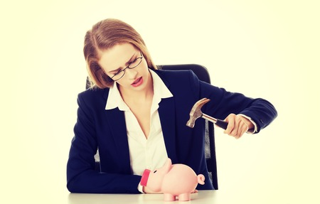 Beautiful business woman is trying to destroy piggy bank with hammer. Isolated on white. photo