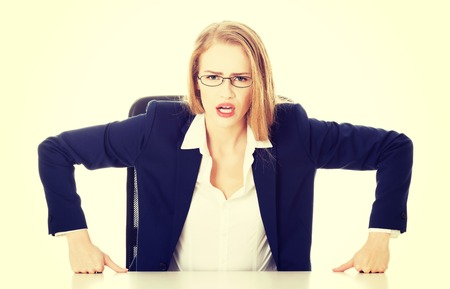 bossy: Attractive business woman by the table, bossy behaviour. Isolated on white.
