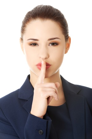 Hush. Businesswoman with finger on her lips gesturing for quiet photo