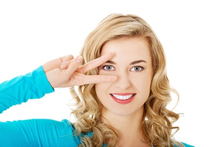 Young woman showing two fingers,victory sign, positive or peace gesture photo