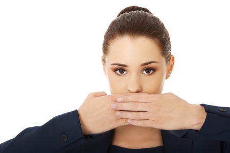 Portrait of young businesswoman covering with hand her mouth photo