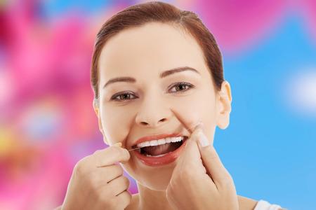 flossing: Beautiful woman flossing her teeth