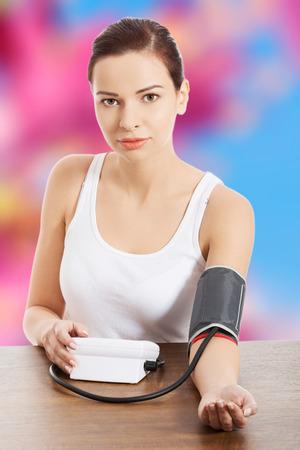 self exam: Young beautiful woman measuring pressure Stock Photo