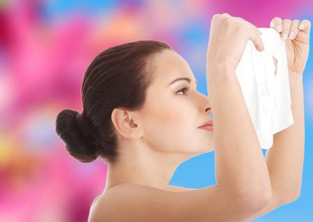 Young beautiful woman getting facial mask photo