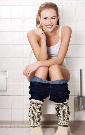 Junge Frau sitzt auf einer Toilette Lizenzfreie Bilder
