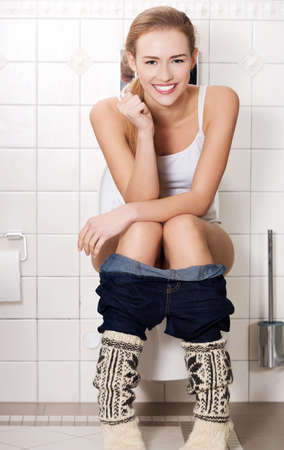 Young woman sitting on a toilet Stock Photo