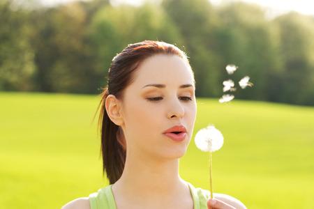 Woman blowing on a dandelion. photo