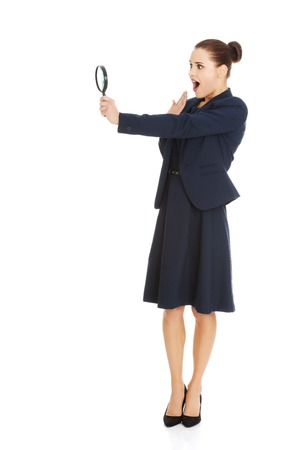 enlargement: Young smiling business woman looking into a magnifying glass.