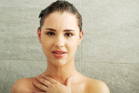 Beautiful fit woman taking shower photo
