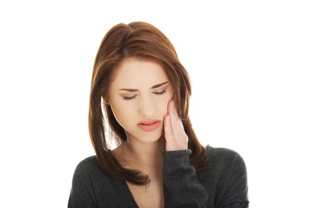 head ache: Teen woman pressing her bruised cheek with a painful expression Stock Photo