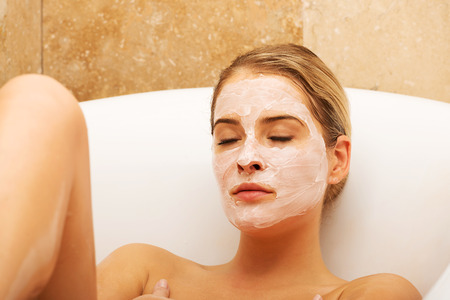 relaxion: Woman relaxing in bath with face mask.