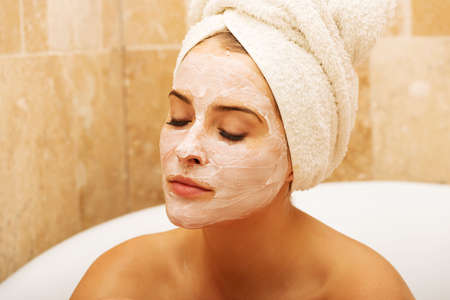 face: Portrait of relaxing woman with closed eyes and cream lotion on face