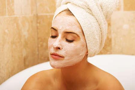tratamientos faciales: Retrato de la mujer de relax con los ojos cerrados y loci�n crema en la cara