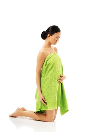 full length woman: Full length woman kneeling wrapped in towel.